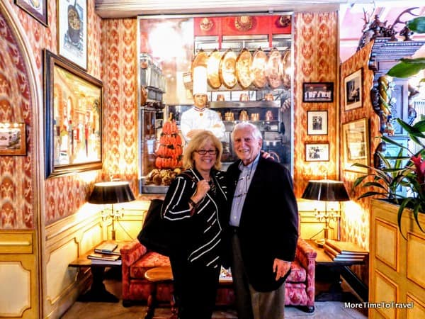 Irene and Jerry outside the dining room, in front of a mural of Paul Bocuse